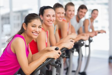 Fit young people working out at spinning class