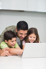 Father with young kids using laptop in kitchen