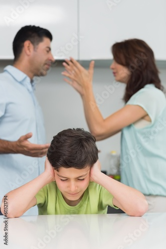 Boy covering ears while parents quarreling in kitchen