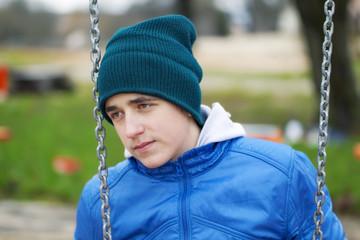 Teenage boy swinging in the park