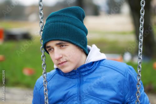 Teenage boy swinging in the park