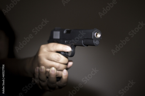 Hand holding gun preparing to fire