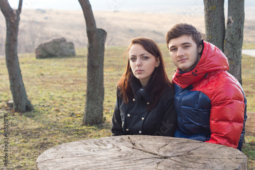 Young couple sitting at a rustic picnic table