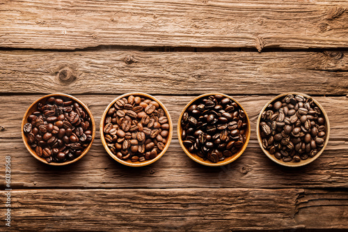 Assorted coffee beans on a driftwood background