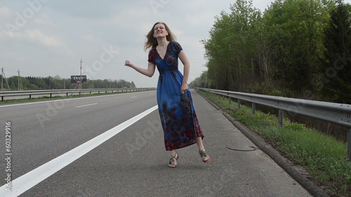 Cheerful smiling woman in blue dress try catch car highway road