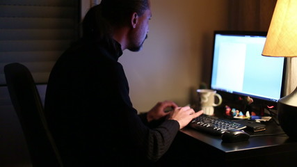 man working computer at home office night time
