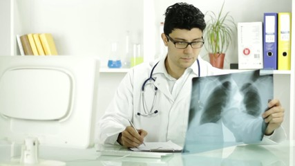 Portrait of smiling doctor looking at xray