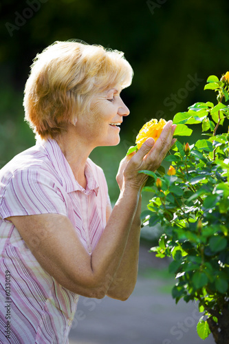 Sentimentality. Mature Old Lady Smelling Yellow Flower