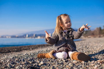 Adorable little girl on the beach in a cozy sweater and dress at