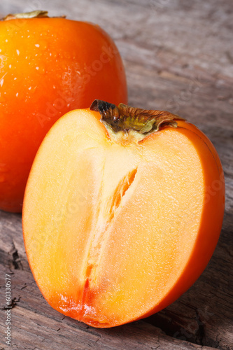 whole and half persimmon closeup on a wooden table.