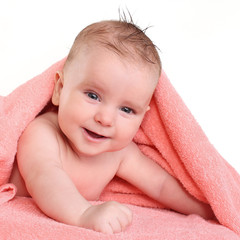 smiling baby after bathing naked wet hair lying on a pink towel
