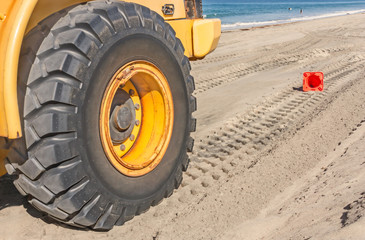 Large tractor tire tread tracks in sand on the beach