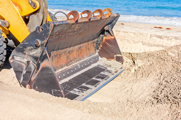 Tractor shovel on sandy beach, close up