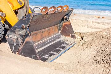 Tractor shovel on sandy beach, close up
