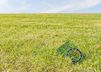 Plastic compass on green grass field,blue sky,cloud background