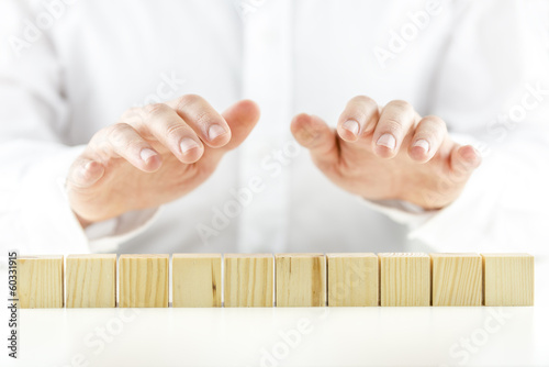 Man holding protective hands above ten wooden cubes