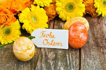 Rosen, Gerbera, Ostereier mit Anhänger auf Holz, Frohe Ostern