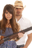cowboy behind woman with gun serious