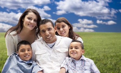 Hispanic Family Portrait Sitting in Grass Field