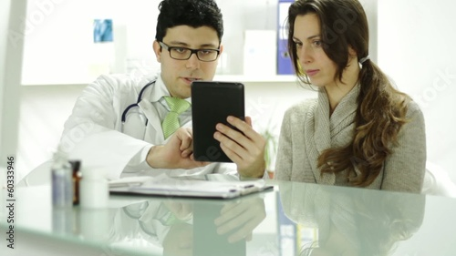 Young Medical Doctor Using Tablet Showing Woman Patient