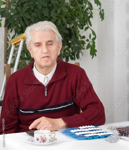 Portrait of senior man with pills