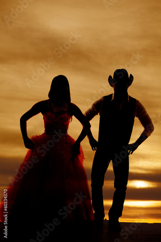 silhouette couple stand hands hips
