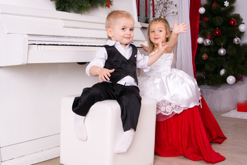 boy and girl sitting near white piano