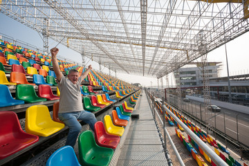 Screaming  man with hands up in the seats for spectators