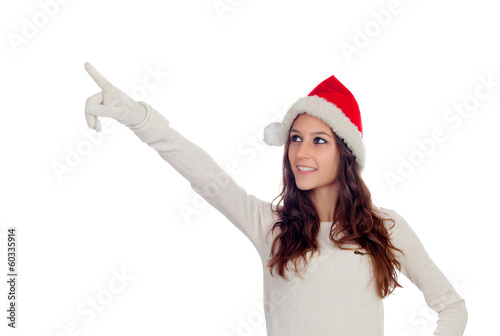 Attractive casual girl with Christmas hat pointing something