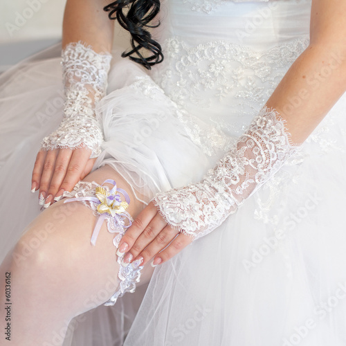 Bride corrects garter on her leg