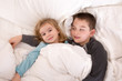 Protective young boy in bed with his little sister