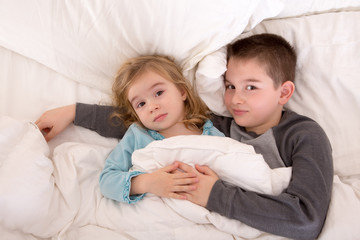 Affectionate young brother and sister lying in bed