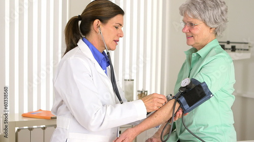 Senior doctor checking elderly patient's blood pressure