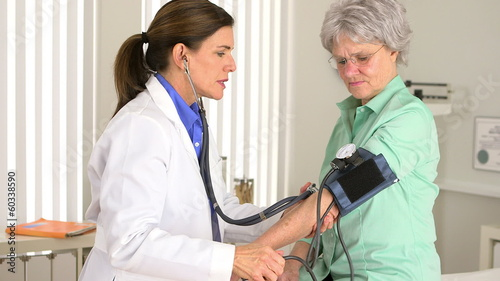 Senior doctor checking blood pressure of patient