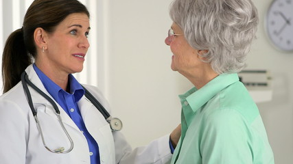 Senior doctor having a positive conversation with elderly patien