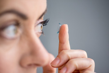Attractive mature lady putting on contact lenses in her eyes