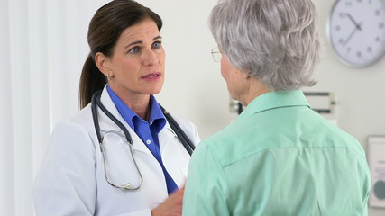 Senior woman doctor talking to elderly patient