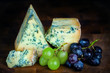 Stilton mature blue mouldy cheese - Dark background and grapes