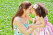 Mother and little daughter rub noses on sunny grassy lawn