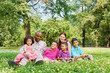Interracial family of six sits on grass on lawn in park