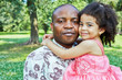 Portrait of african father who stands, holding little daughter