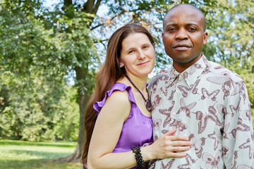 Interracial couple stands embracing in summer park