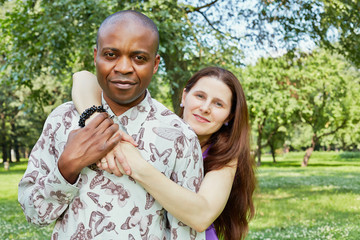 Mixed race smiling couple stands embracing in summer park