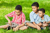 Portrait of three boys-brothers who sit together on grass