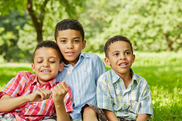 Portrait of three smiling boys-brothers who sit together