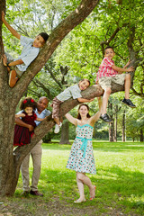 Family of six takes rest in park, boys climb on tree