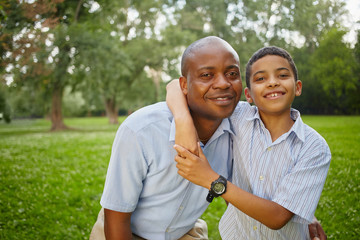 Half-length portrait of smiling african father and son standing
