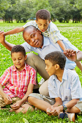 Closeup portrait of father and his three sons on green lawn