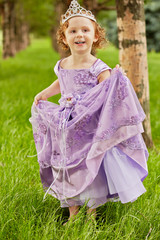Little girl in beautiful violet gown and crown on head stands