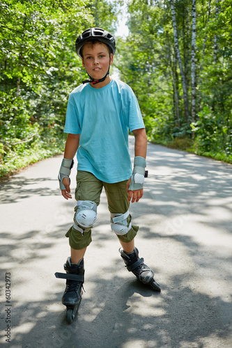 Teenage boy roller-skates on walkway in park
